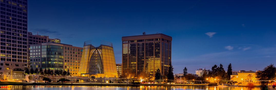 """Oakland, California. Evening view across Lake Merritt with beautiful reflections of buildings and lights on the water. The """"Necklace of Lights"""" illuminates the pedestrian walk around the lake. Copy space."""